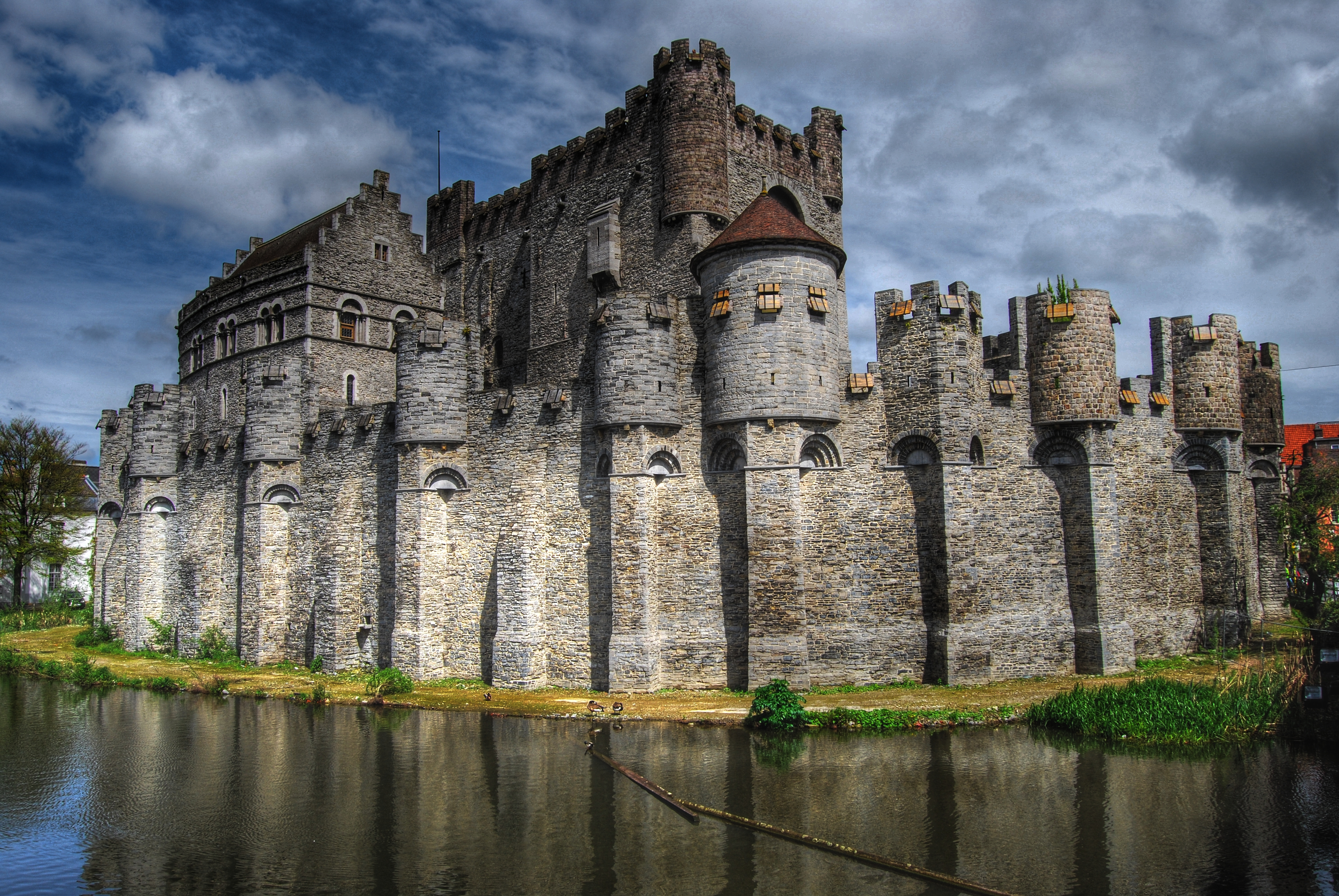 imposing castle of grey stone surrounded by moat