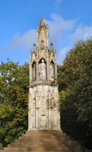 Ston cross with female figure and the top half of the spire missing