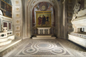 Ornate chapel with intricately tiled floor and marble wall panels