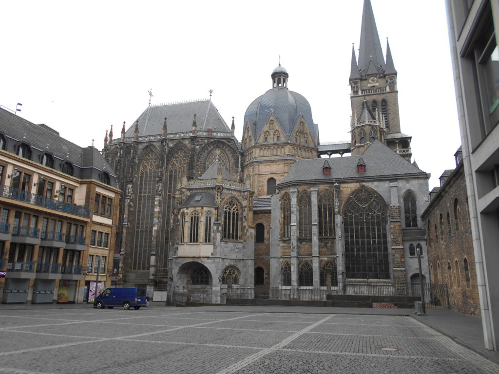 The courtyard and exterior of Aachen cathedral, showing many domes and spires