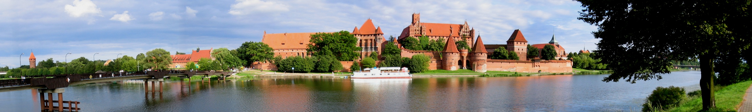 Panorama of a grand castle of red brick on a riverbank