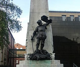 A statue of a soldier standing on top of a dragon